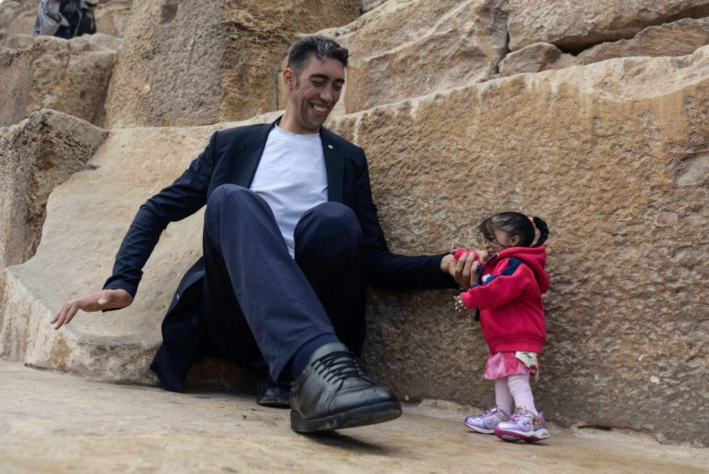 India's Jyoti Amge (R), the world's shortest woman poses for a picture with Sultan Kosen of Turkey, the world's tallest man, at the foot of one of the three Pyramids of Giza in Egypt on January 26, 2018. / AFP PHOTO / STRINGER